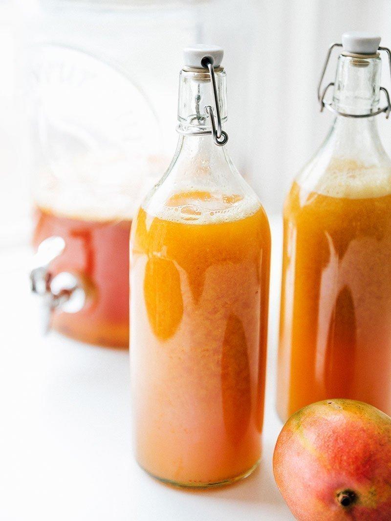 kombucha in bottles with a mango
