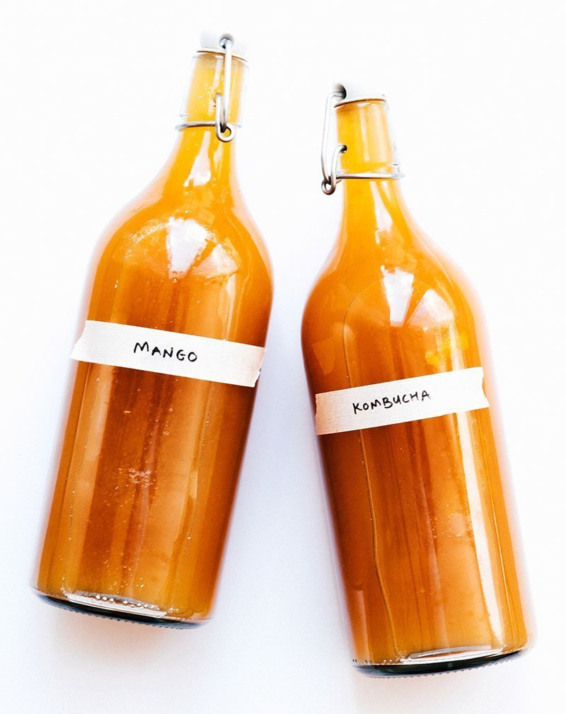 mango kombucha recipe in glass bottles
