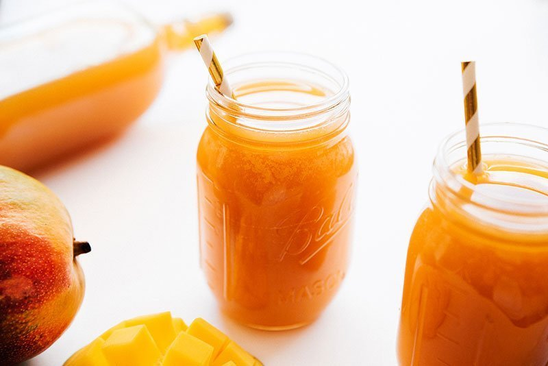 homemade mango kombucha recipe in a mason jar with straws and mangos