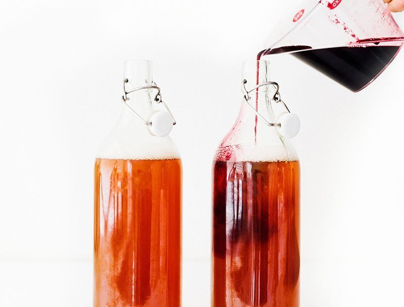 pouring blueberry kombucha ingredients into fermentation bottles