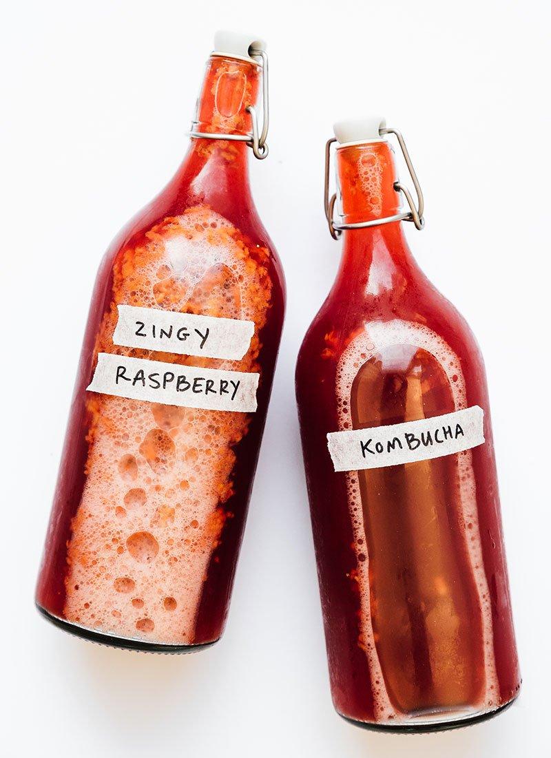 Raspberry kombucha in bottles on white background