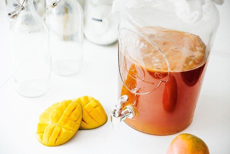mango kombucha in large glass jar with mangos