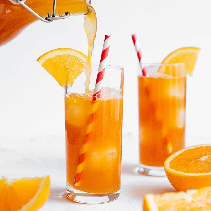 Pouring vanilla orange kombucha into a glass