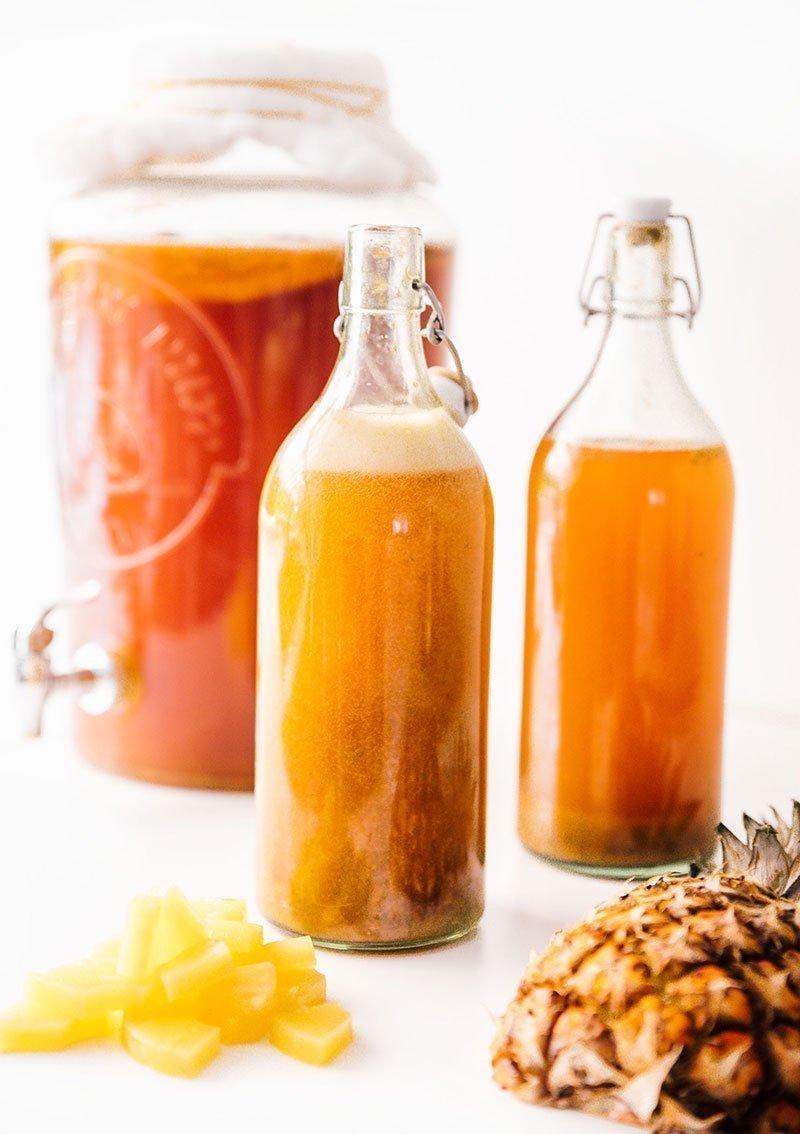 pineapple basil kombucha in glass jar and fermentation bottles