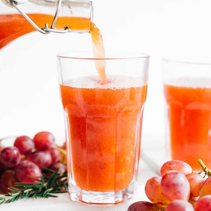 Pouring kombucha into a glass with grapes