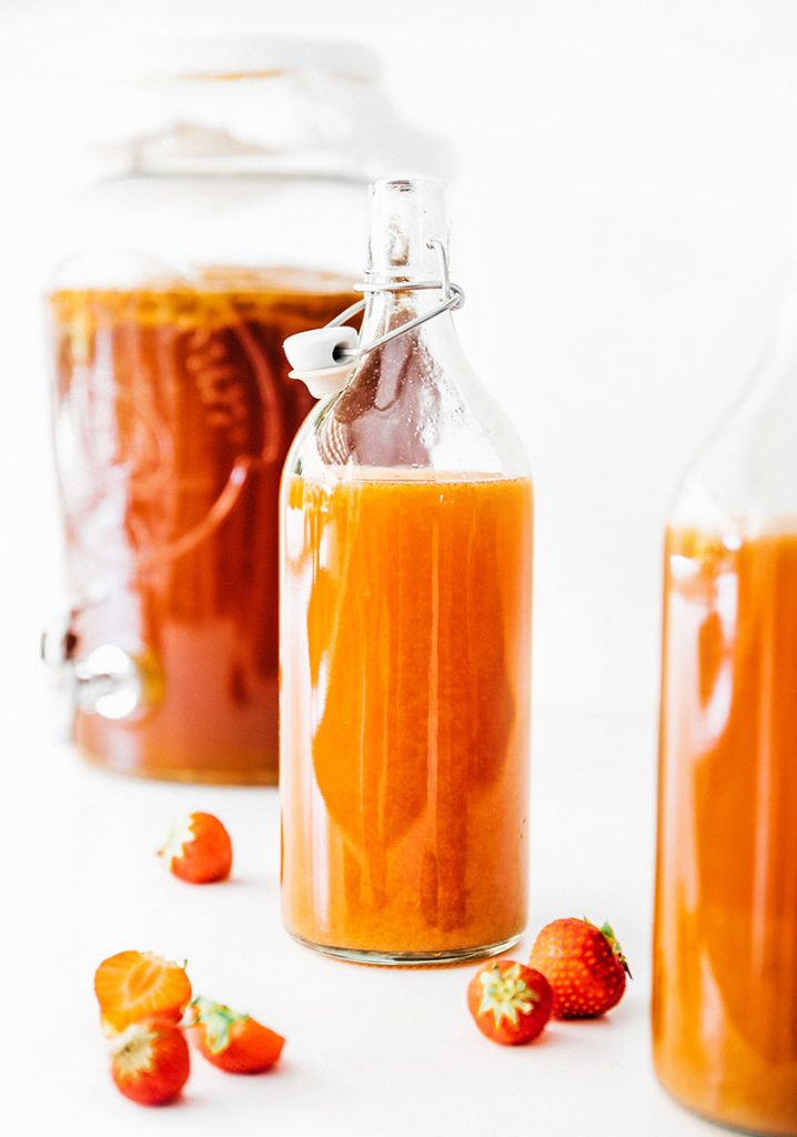 kombucha in fermentation bottles with strawberries