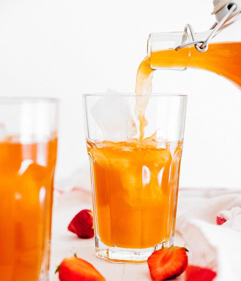 pouring strawberry kombucha into glass