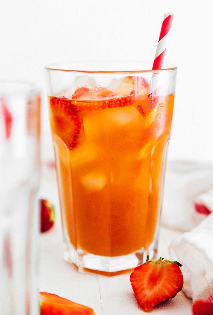 strawberry in kombucha in glass with straw