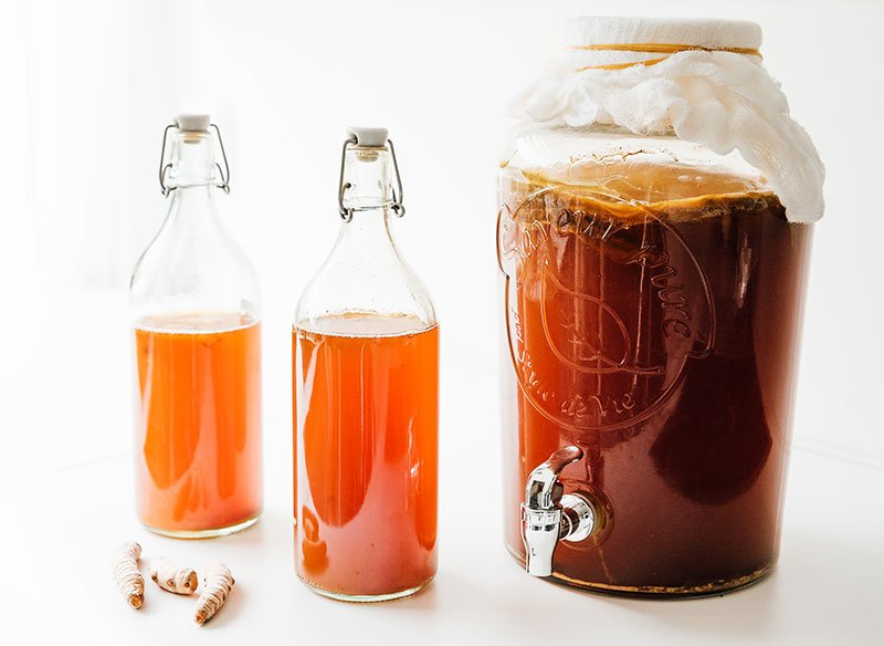 Turmeric kombucha in bottles on white background