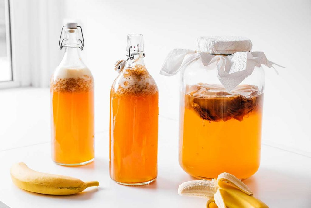 Banana with bottles of kombucha on white background