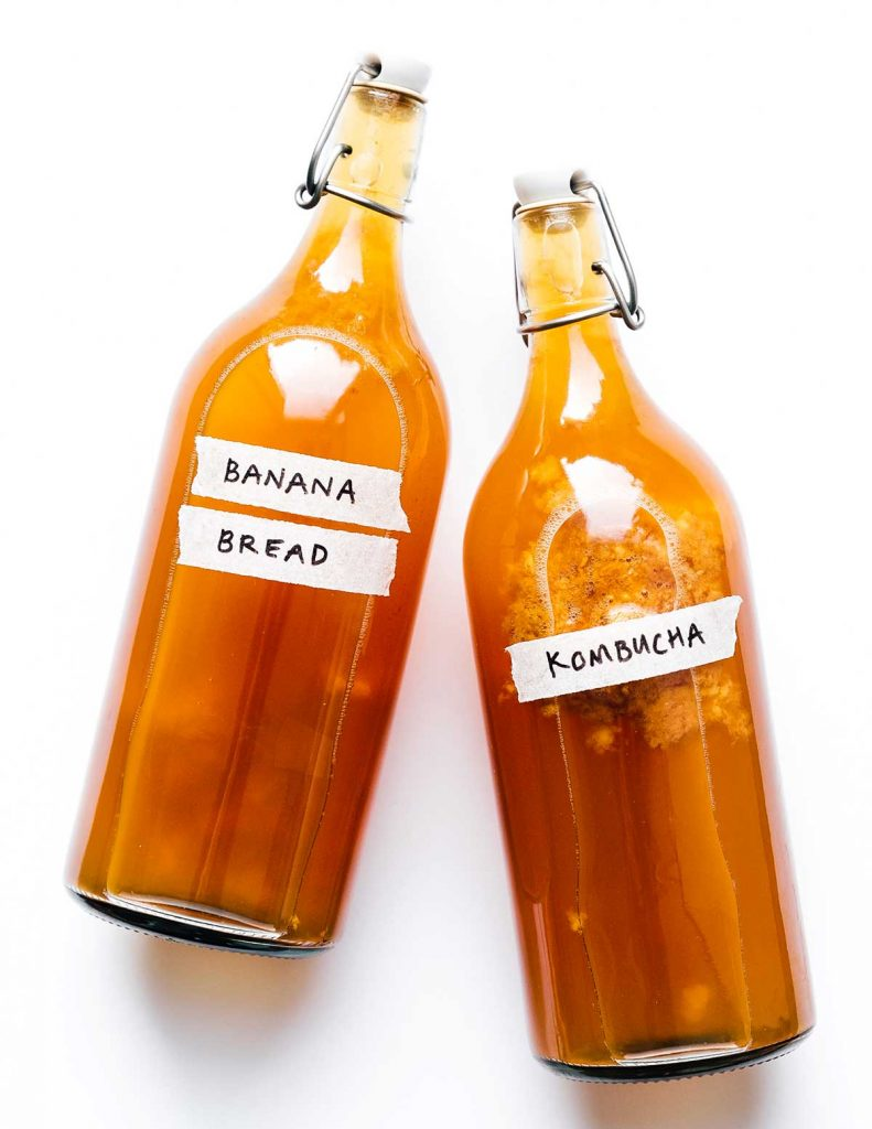 Banana bread kombucha in fermentation bottles on a white background