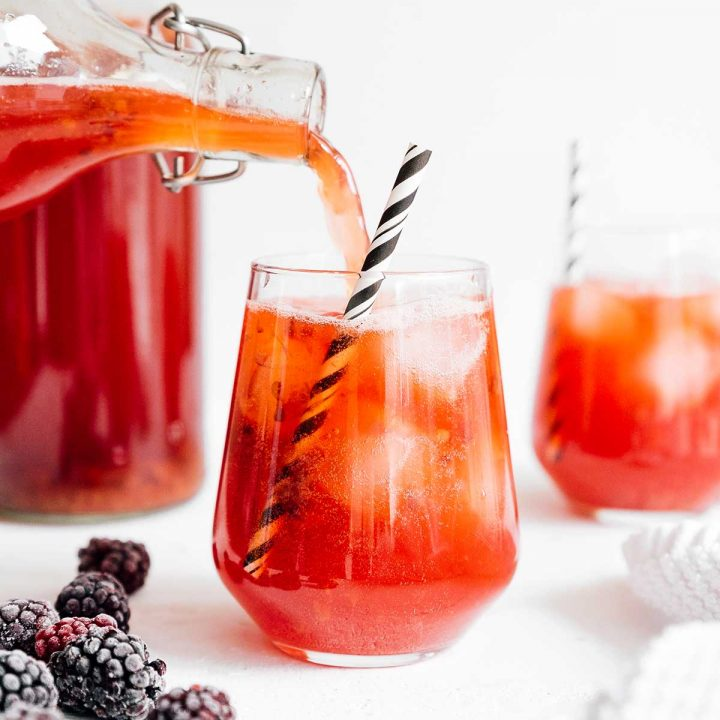 Pouring berry vanilla kombucha in a glass with a paper straw on white background