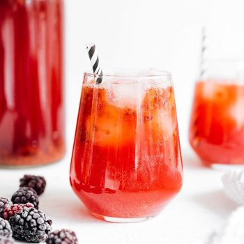Blackberry kombucha in a glass with a paper straw on white background