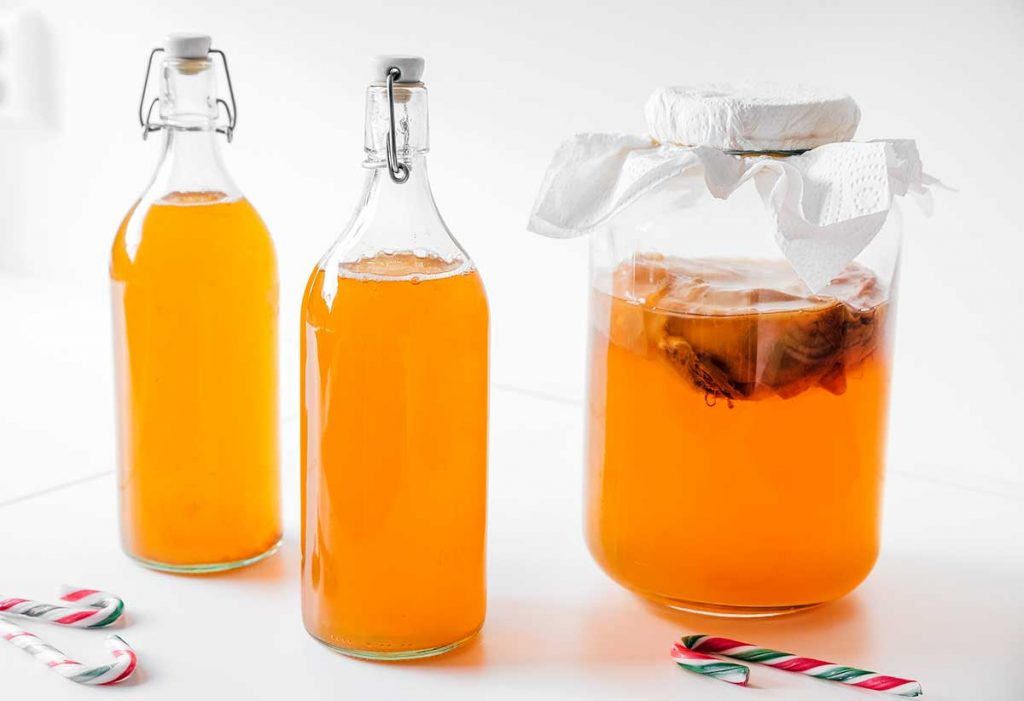 Candy cane kombucha in fermentation bottles on white background