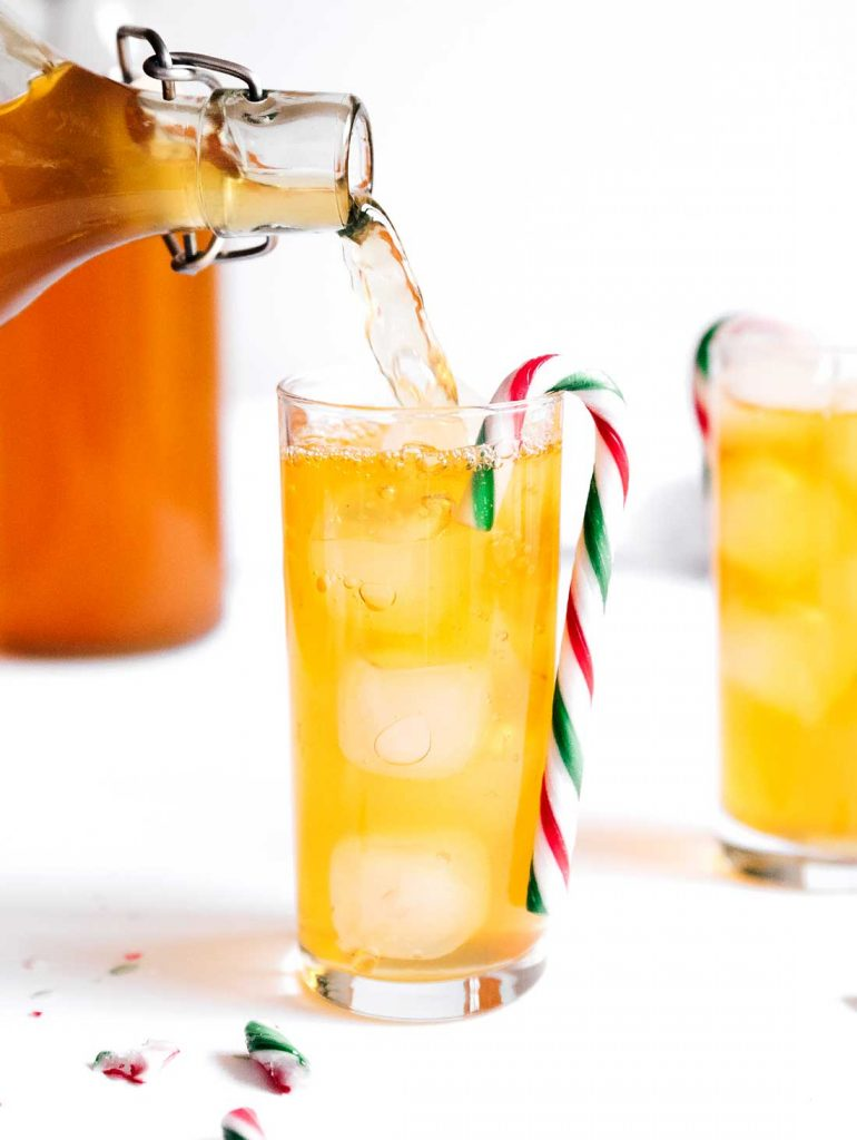 Pouring kombucha into a glass with a candy cane