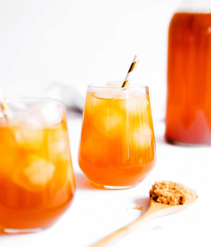 Kombucha in a glass with ice and a paper straw