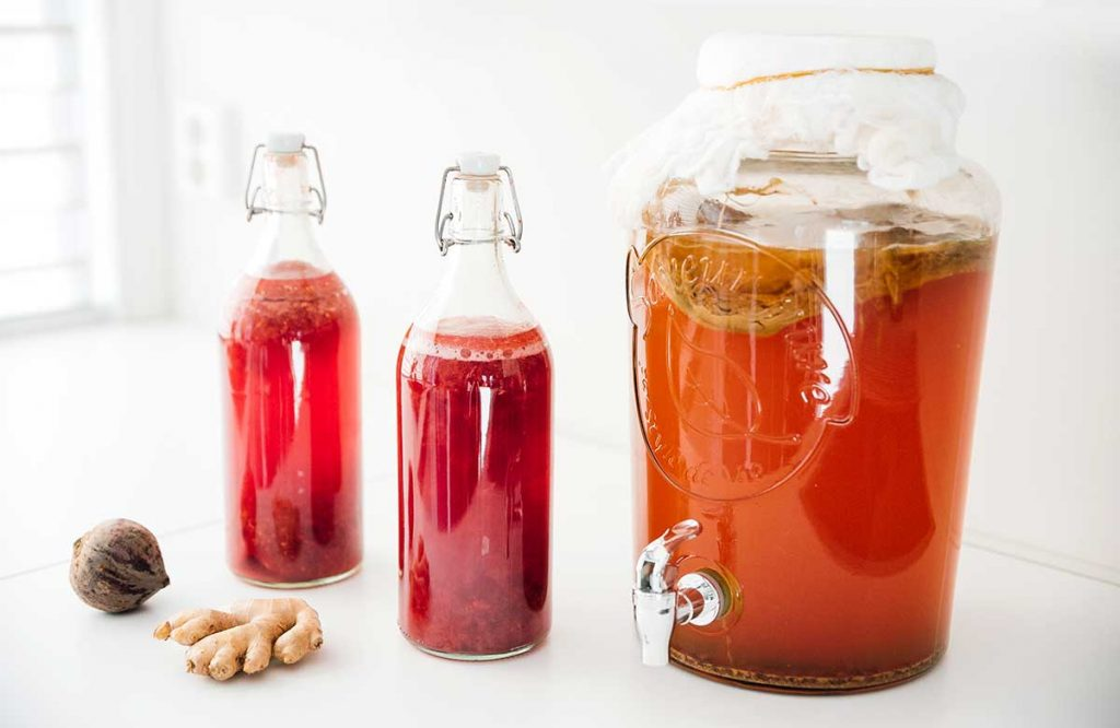 Ginger beet kombucha in fermentation bottles on a white background