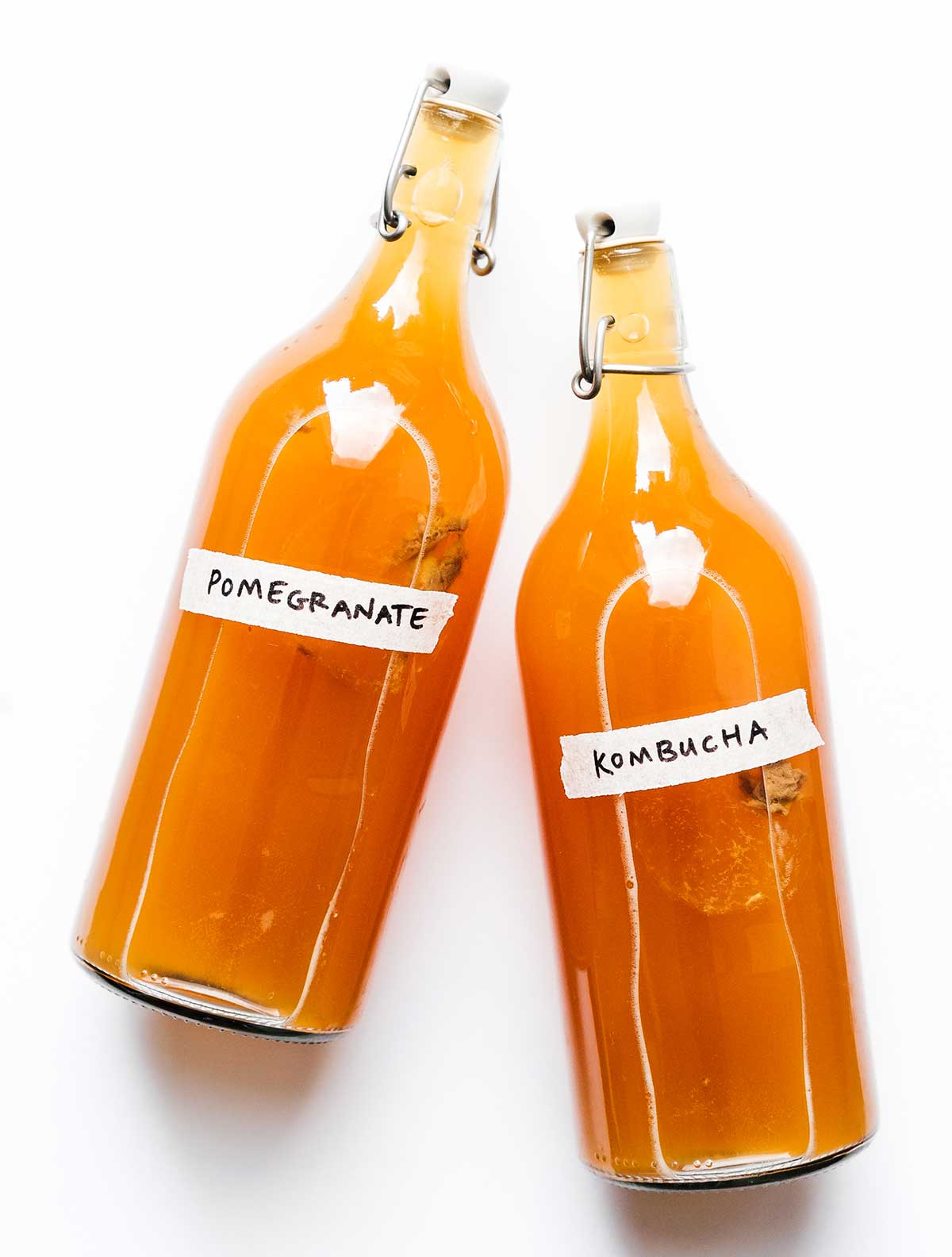 Pomegranate kombucha in fermentation bottles on white background