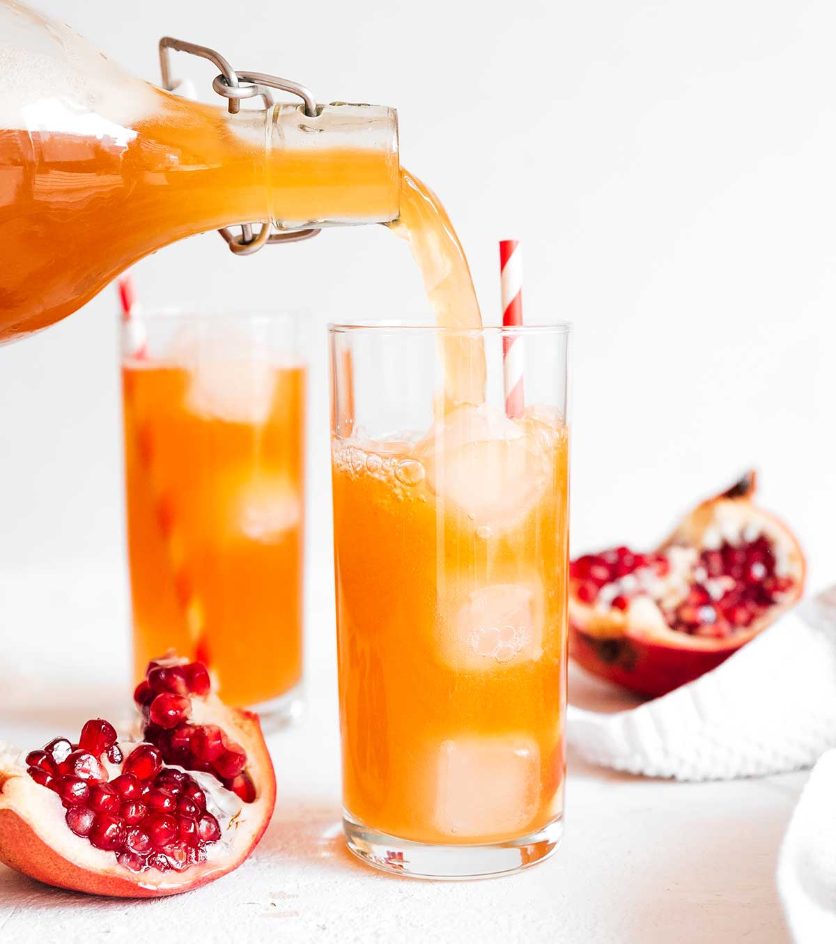 Pouring pomegranate kombucha in a glass on white background