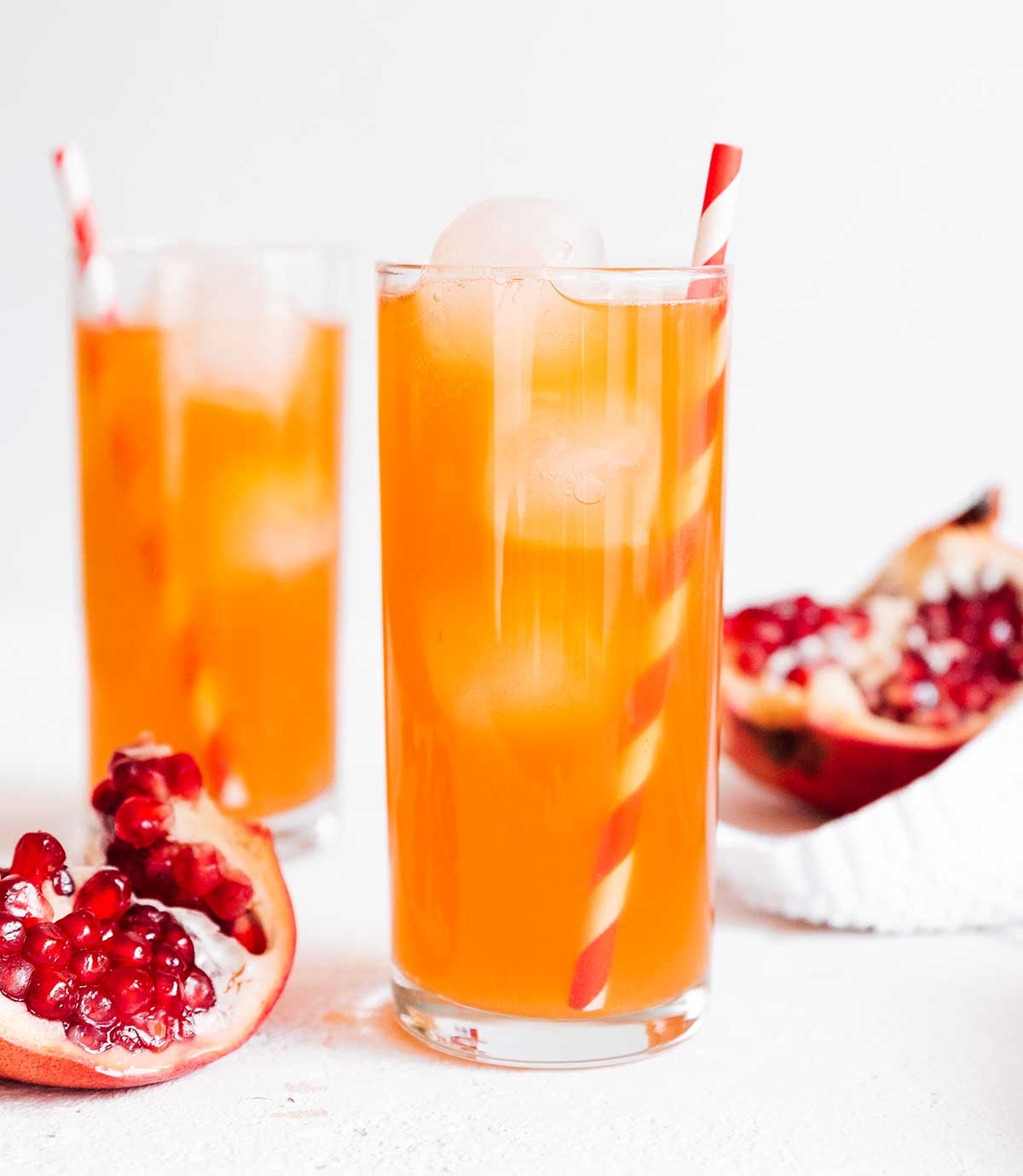 Pomegranate kombucha in a glass on white background