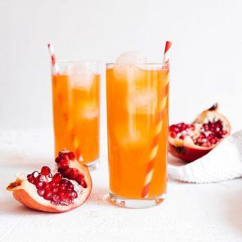 Pomegranate kombucha in a glass on white background
