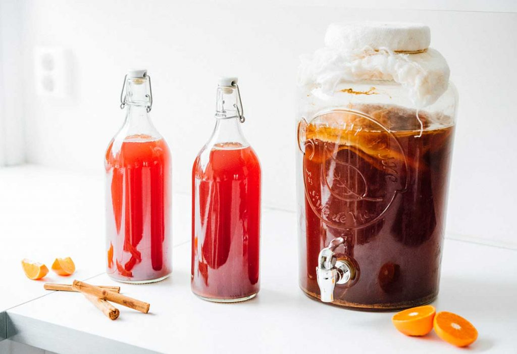 Bottles of red wine kombucha on a white background