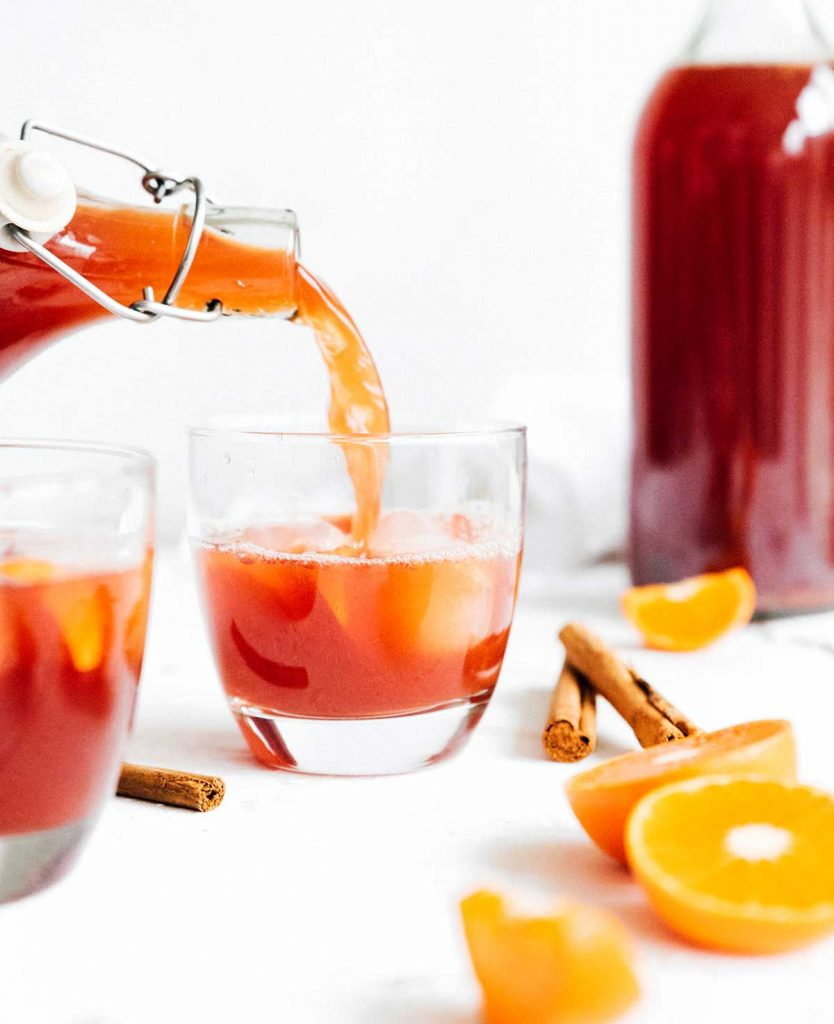 Pouring gluhwein flavored kombucha into a glass with cinnamon sticks and oranges