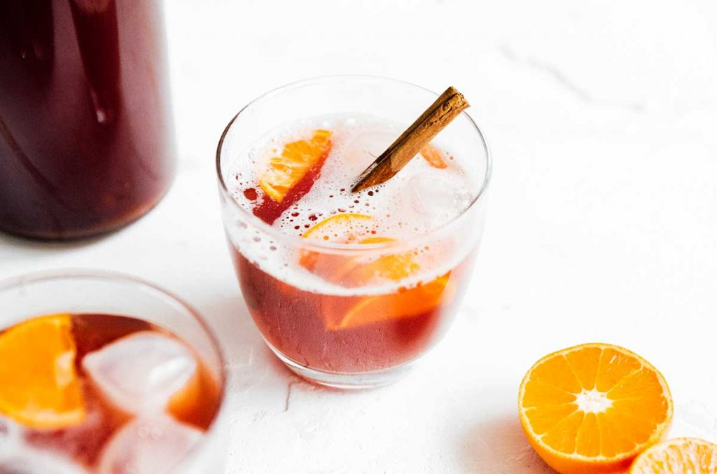 Mulled wine kombucha on a white background with cinnamon and orange