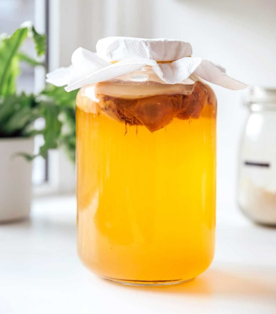 Jar of green tea kombucha with a SCOBY