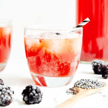 Bubbly lavender kombucha on a white background with blackberries