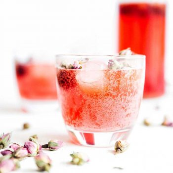 Carbonated rose kombucha in a glass on a white background