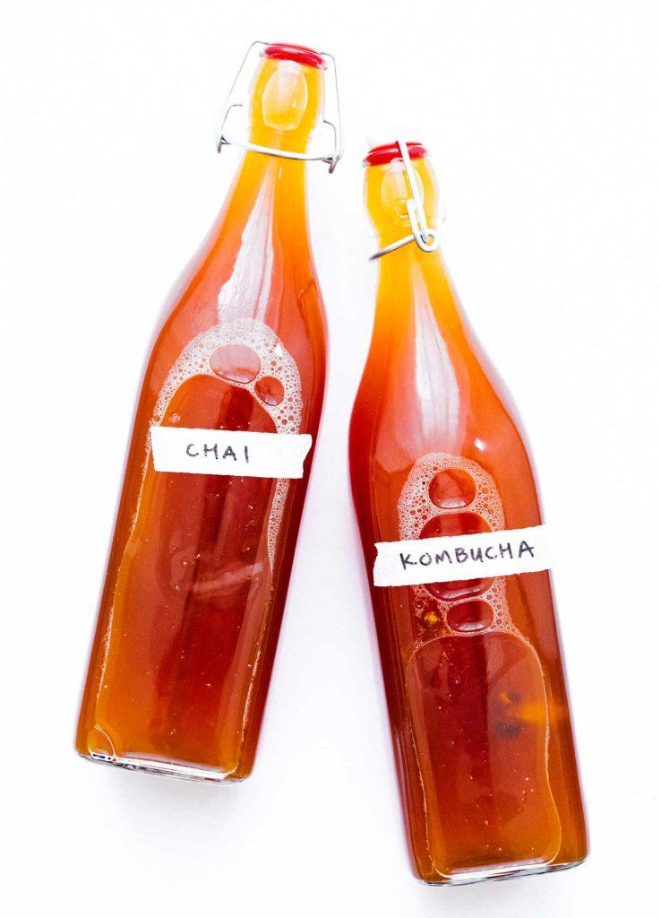 Bottles of chai kombucha on a white background