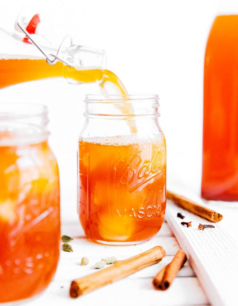 Pouring kombucha into a mason jar