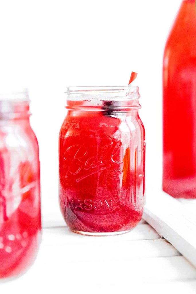 Red kombucha in a ball mason jar on a white background