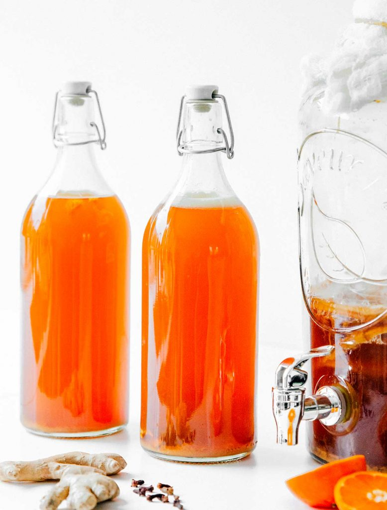 Kombucha in fermentation bottles on a white counter
