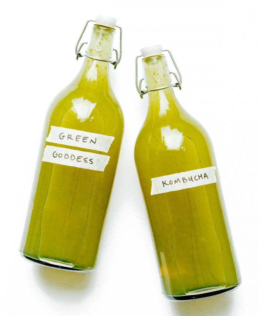 Green goddess kombucha in fermentation bottles on a white background