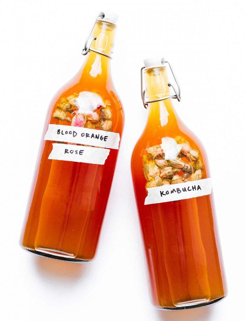 Bottles of blood orange kombucha on a white background