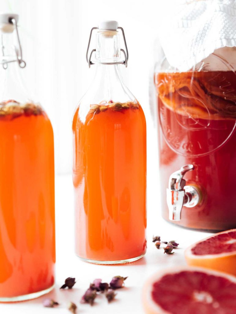 Bottles of blood orange kombucha on a white background