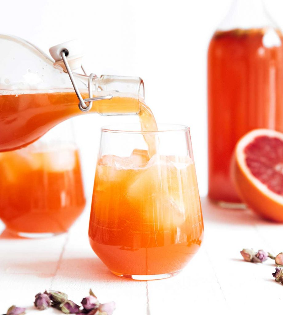 Pouring blood orange kombucha in a glass on a white background