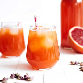 Blood orange kombucha in a glass on a white background