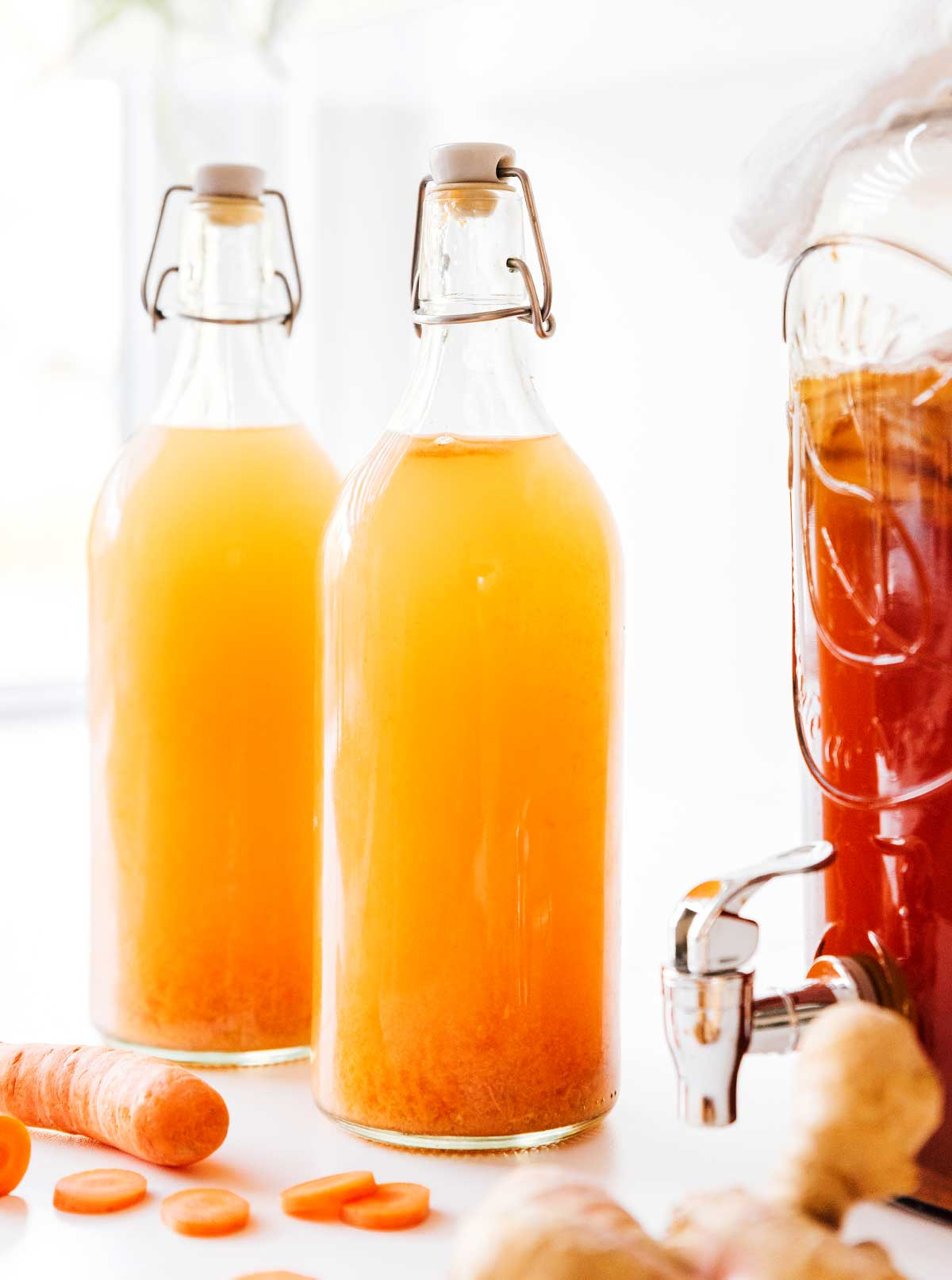 Carrot ginger kombucha in fermentation bottles on an orange background