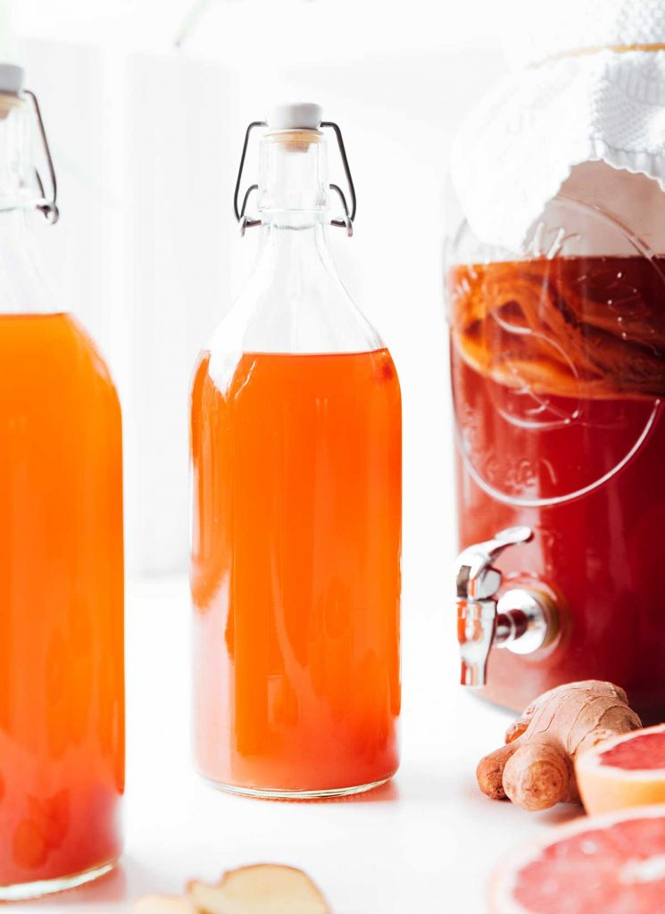 Bottles of grapefruit kombucha on a white background