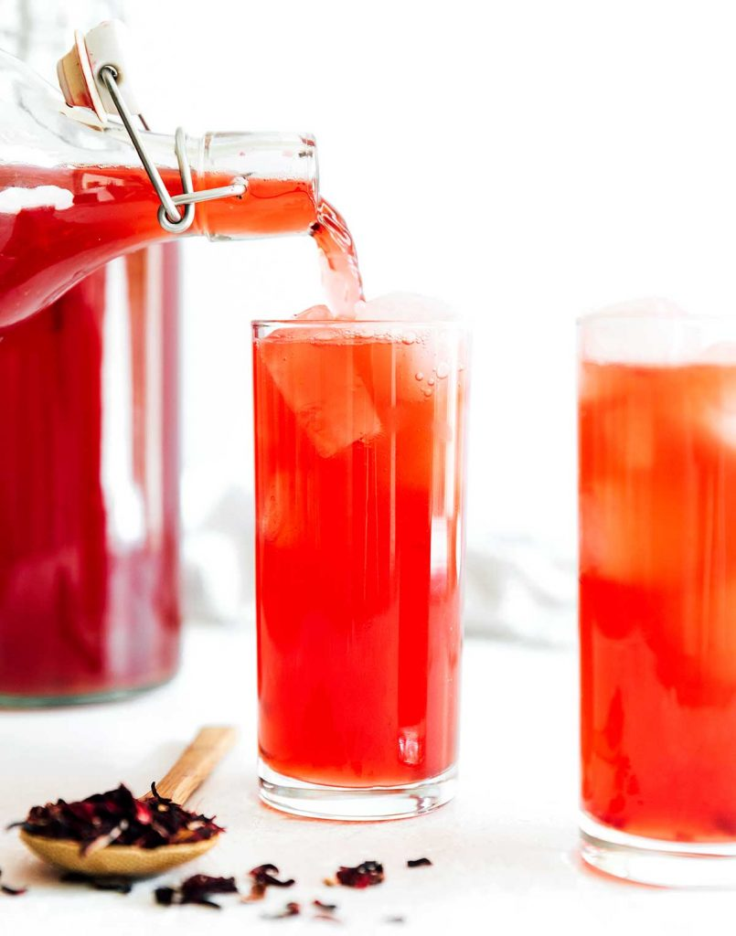 Hibiscus kombucha in a glass with a paper straw