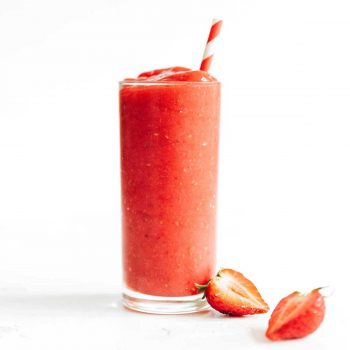 Red smoothie in a tall glass with striped straw and strawberries